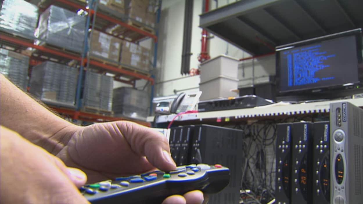 Une main tenant une télécommande de Cogeco devant un écran et de l'équipement des différents services offerts par l'entreprise.