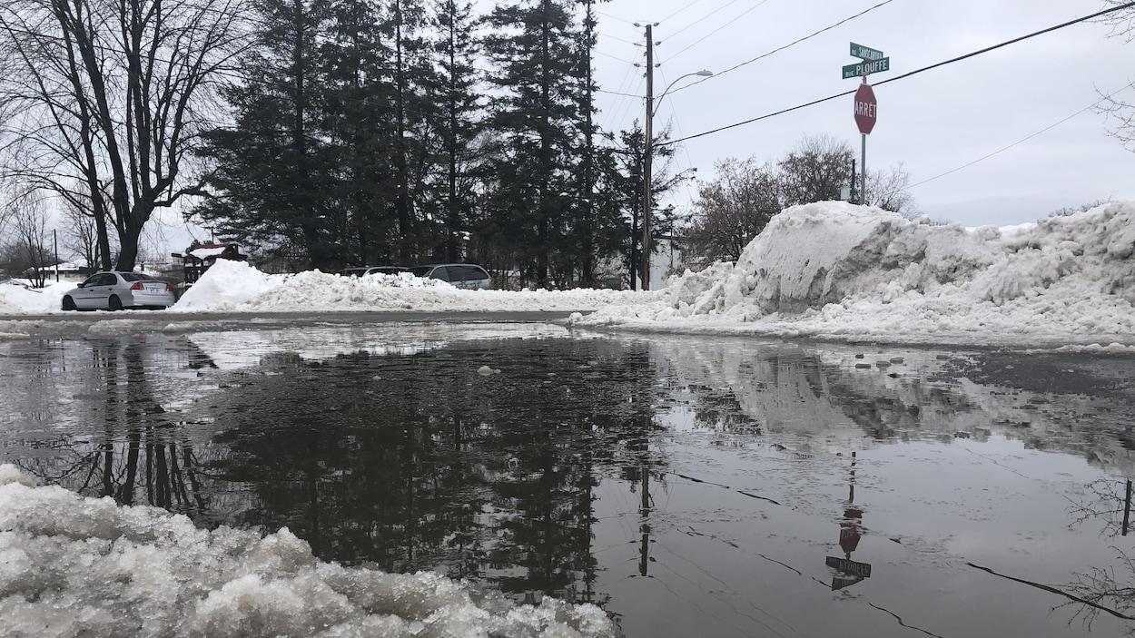 Une grande flaque d'eau sur la chaussée en hiver.