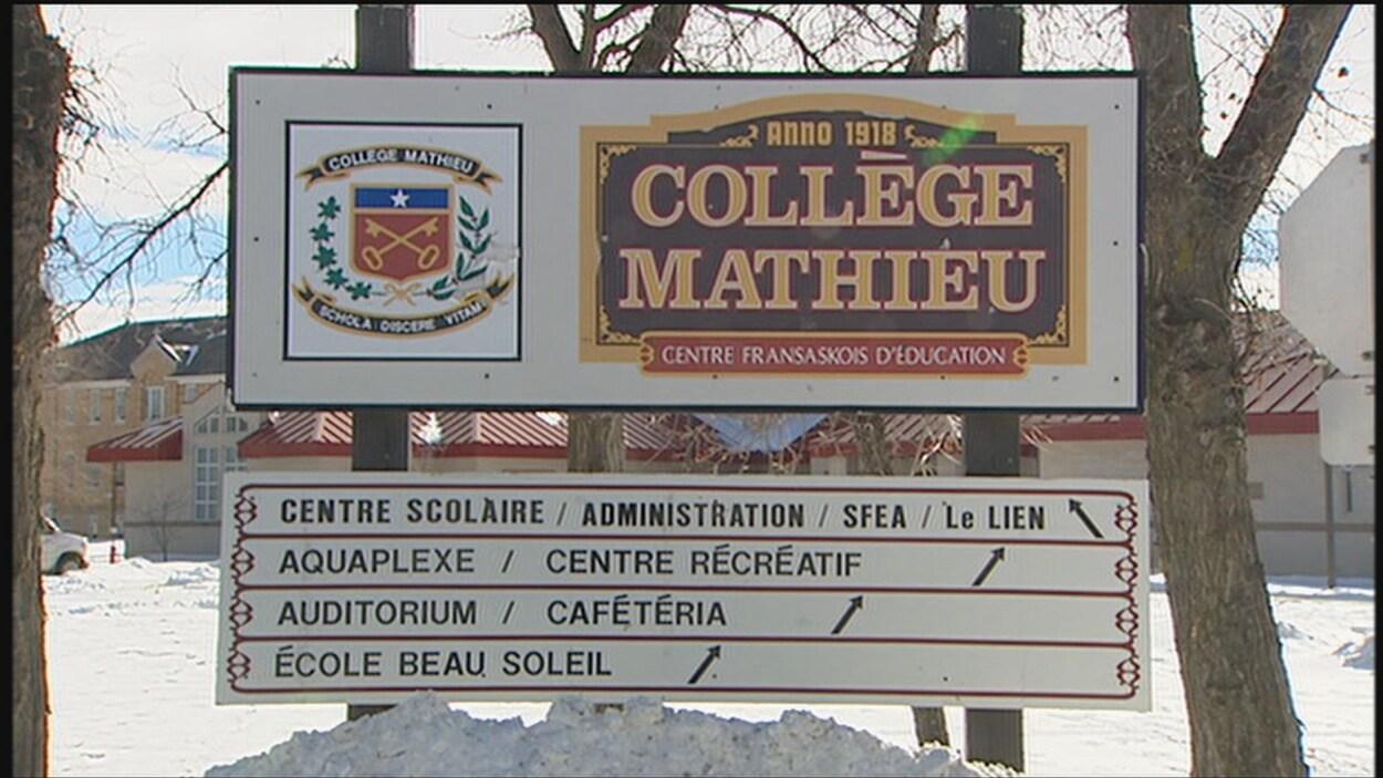 Une grande pancarte affichant la devise du Collège Mathieu avec, en dessous, des indications pour se rendre aux différents pavillons.