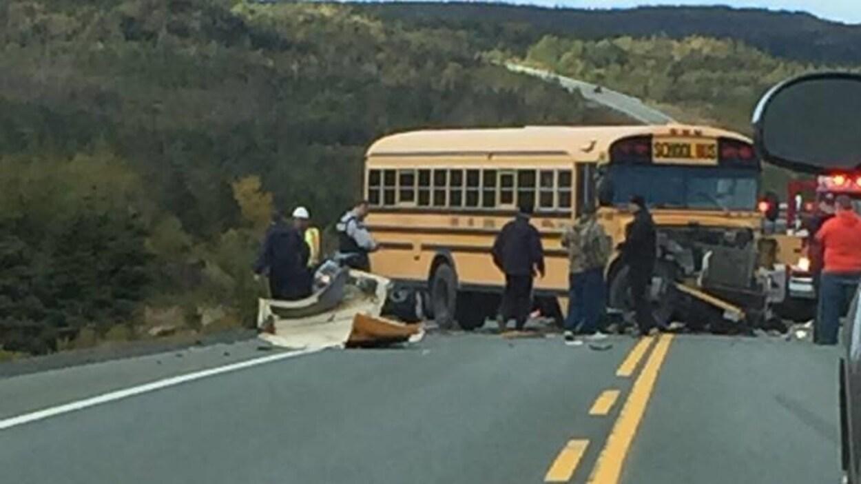 Un policier et des témoins entourent un autobus scolaire à l'avant endommagé et des débris d'un véhicule accidenté sur une route