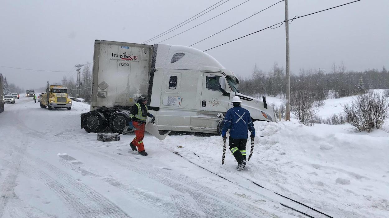 Un camion est pris sur le bord de la route et des véhicules attendent derrière.