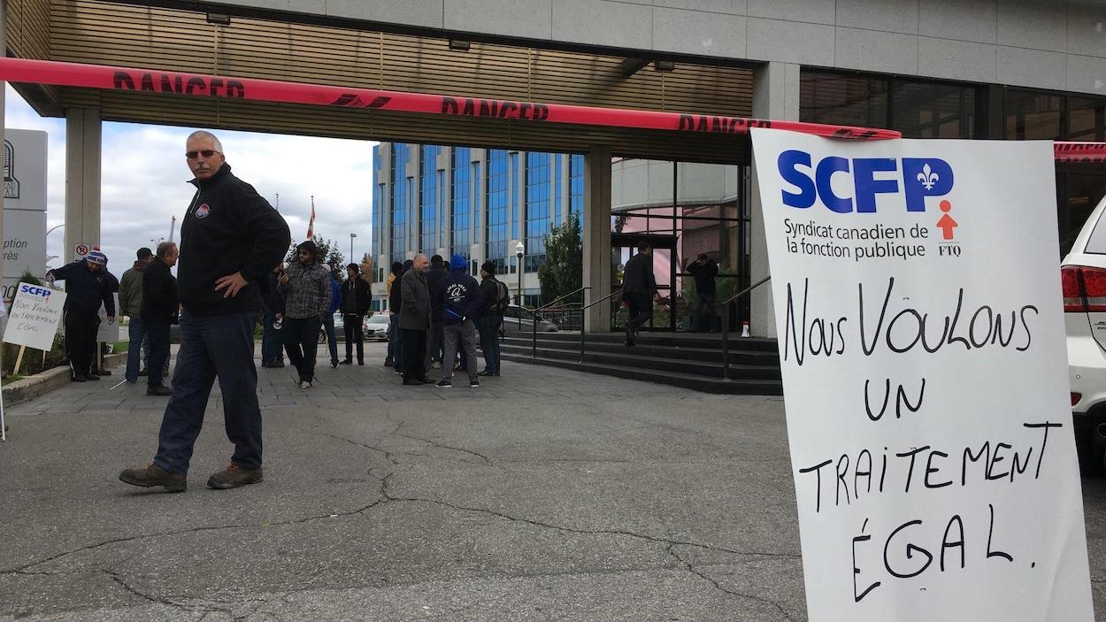 Des cols bleus près d'une pancarte, sur laquelle on a inscrit : « Nous voulons un traitement égal »