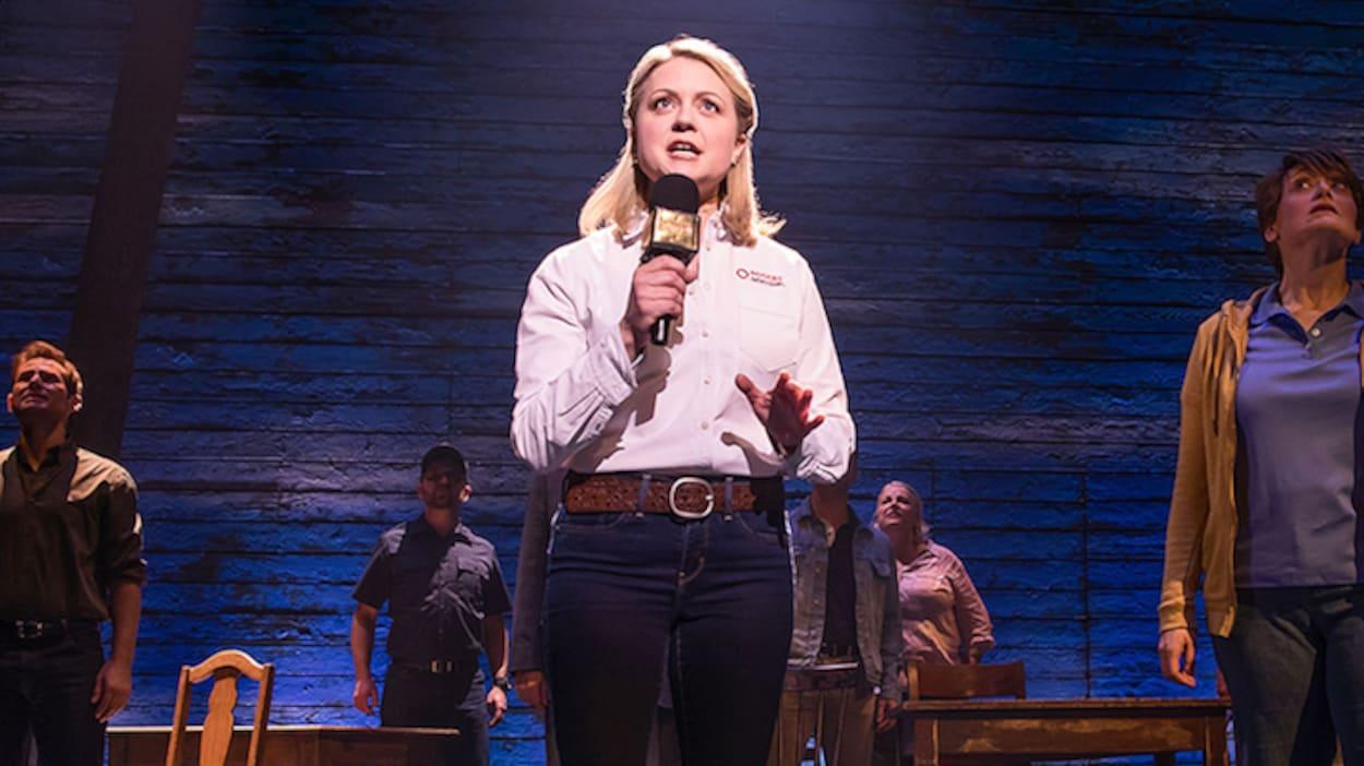 Une scène de la comédie musicale « Come From Away », où l'on peut voir une actrice jouant une journaliste, entourée d'autres acteurs.