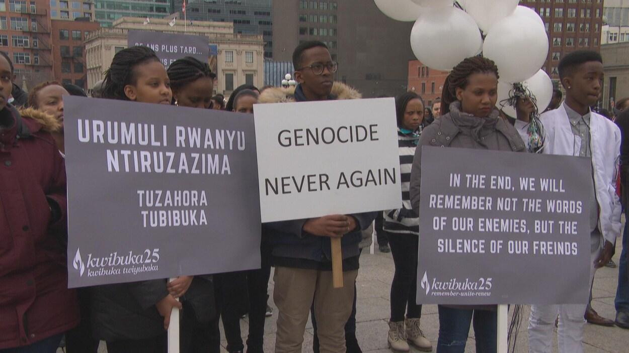 Une foule de gens rassemblés tiennent des pancartes contre les génocides.