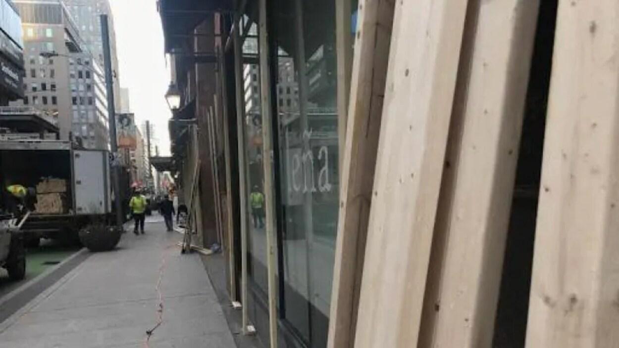 Des madriers appuyés contre la vitrine d'un magasin.