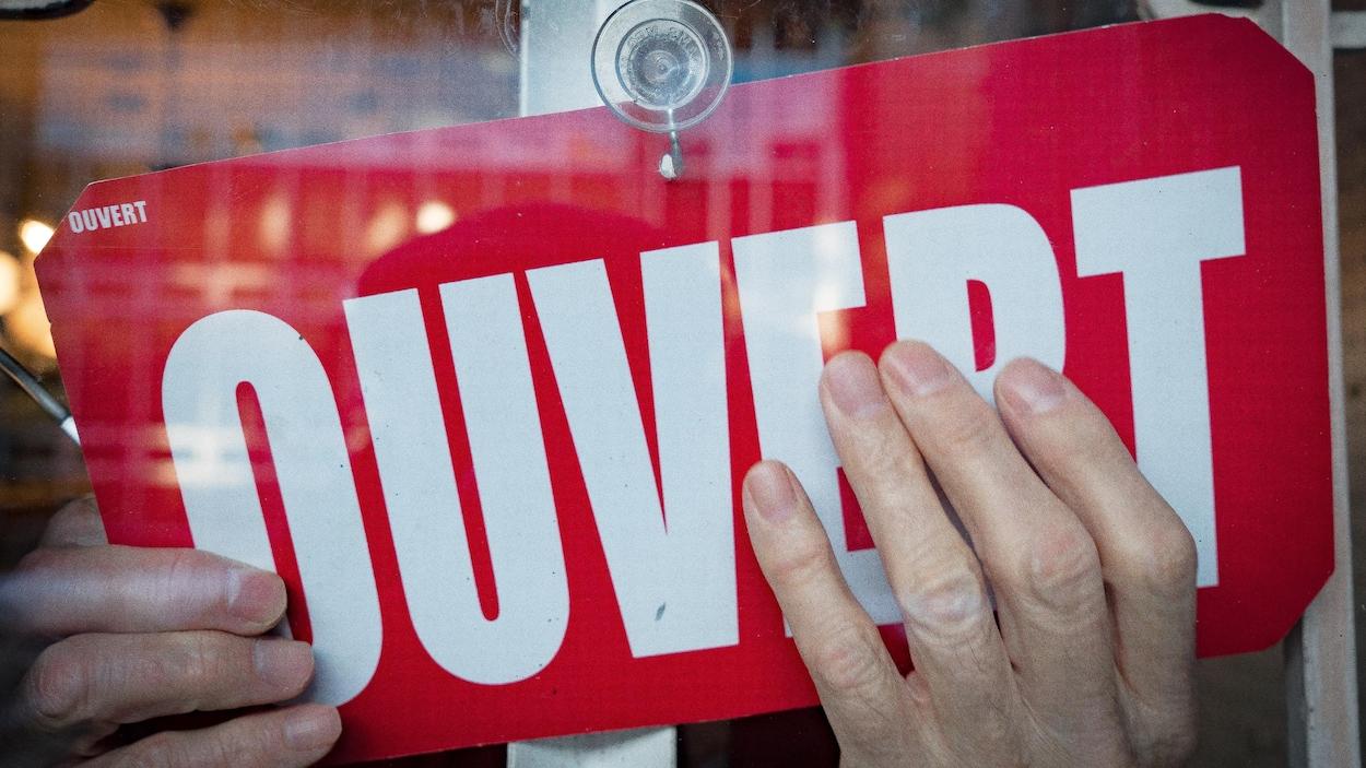 À une fenêtre, des mains placent une affiche indiquant que le magasin est ouvert.