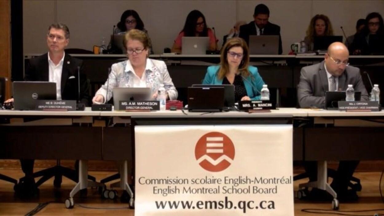 Quatre commissaires sont assis pendant une rencontre.