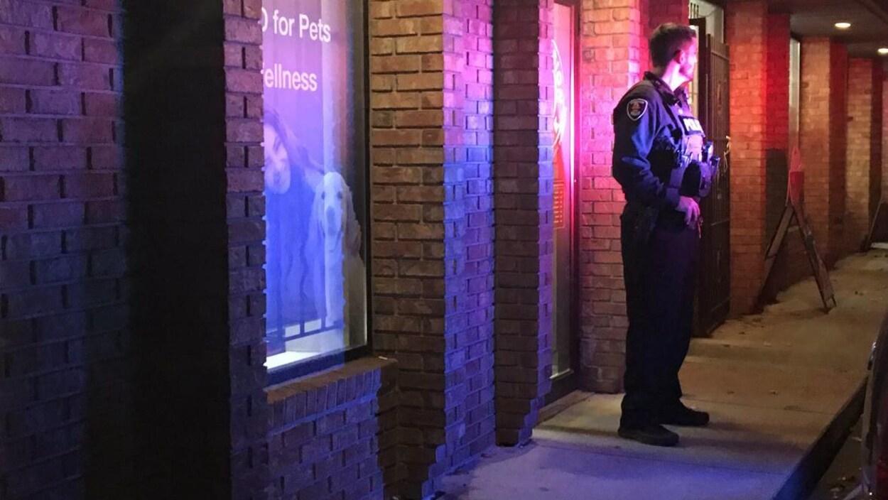 Un policier est devant un magasin la nuit