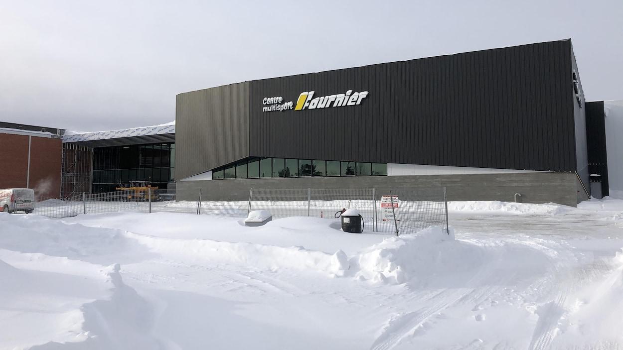 La façade du Complexe Multisport, avec devant une clôture de chantier de construction.