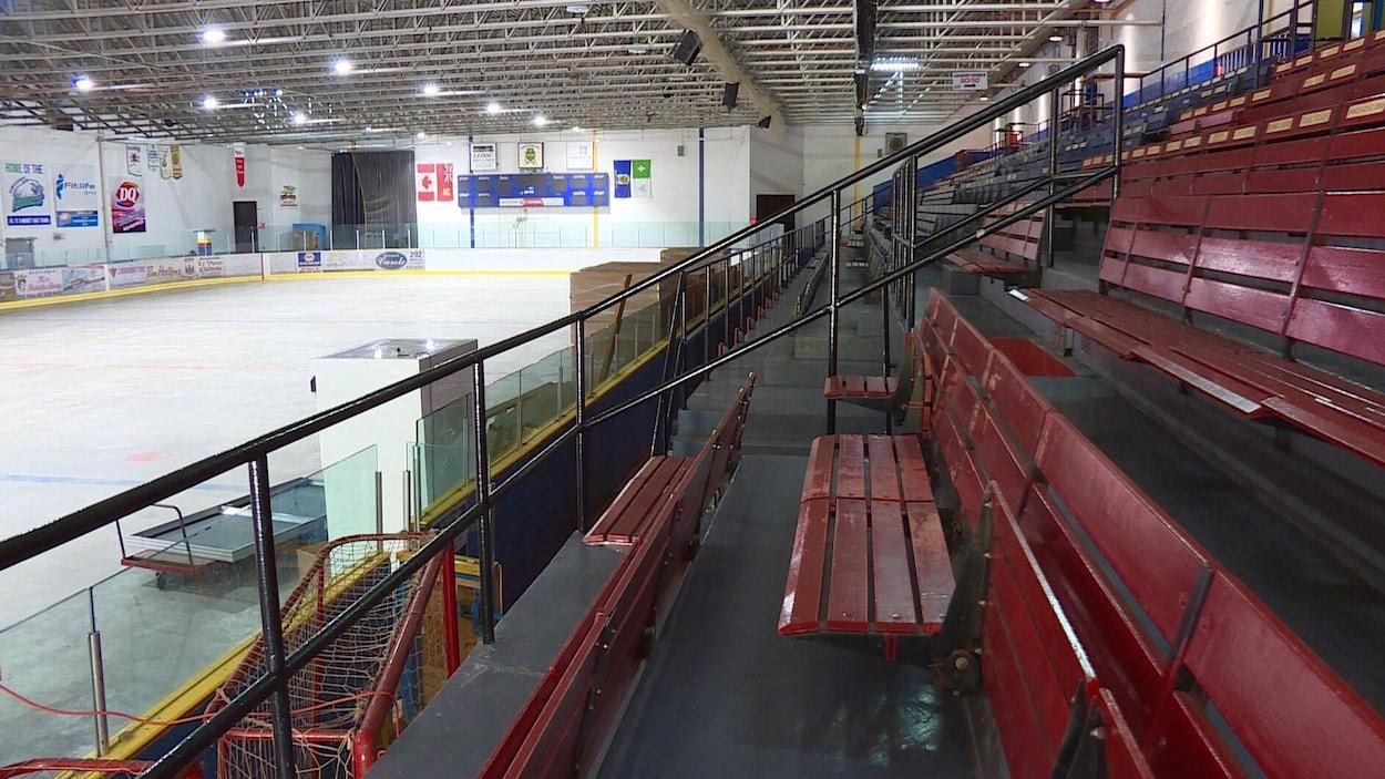 L'intérieur de l'aréna, avec la glace et des bancs rouges.