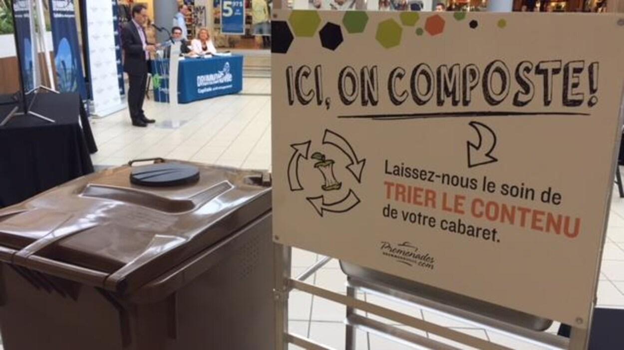 Un grand bac brun de compost à côté d'un chariot porte-plateaux. Une affiche sur laquelle est inscrite «ici, on composte. Laissez-nous le soin de trier le contenu de votre cabaret.»