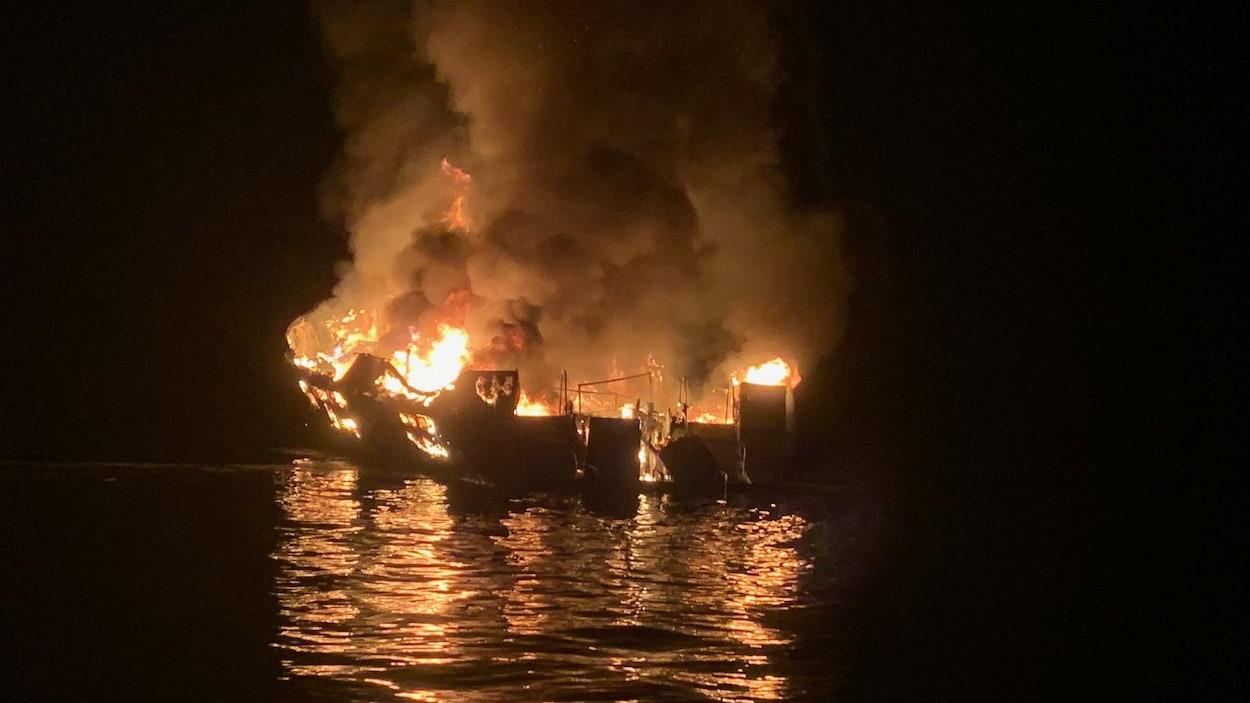 Un bateau ravagé par les flammes en pleine nuit.