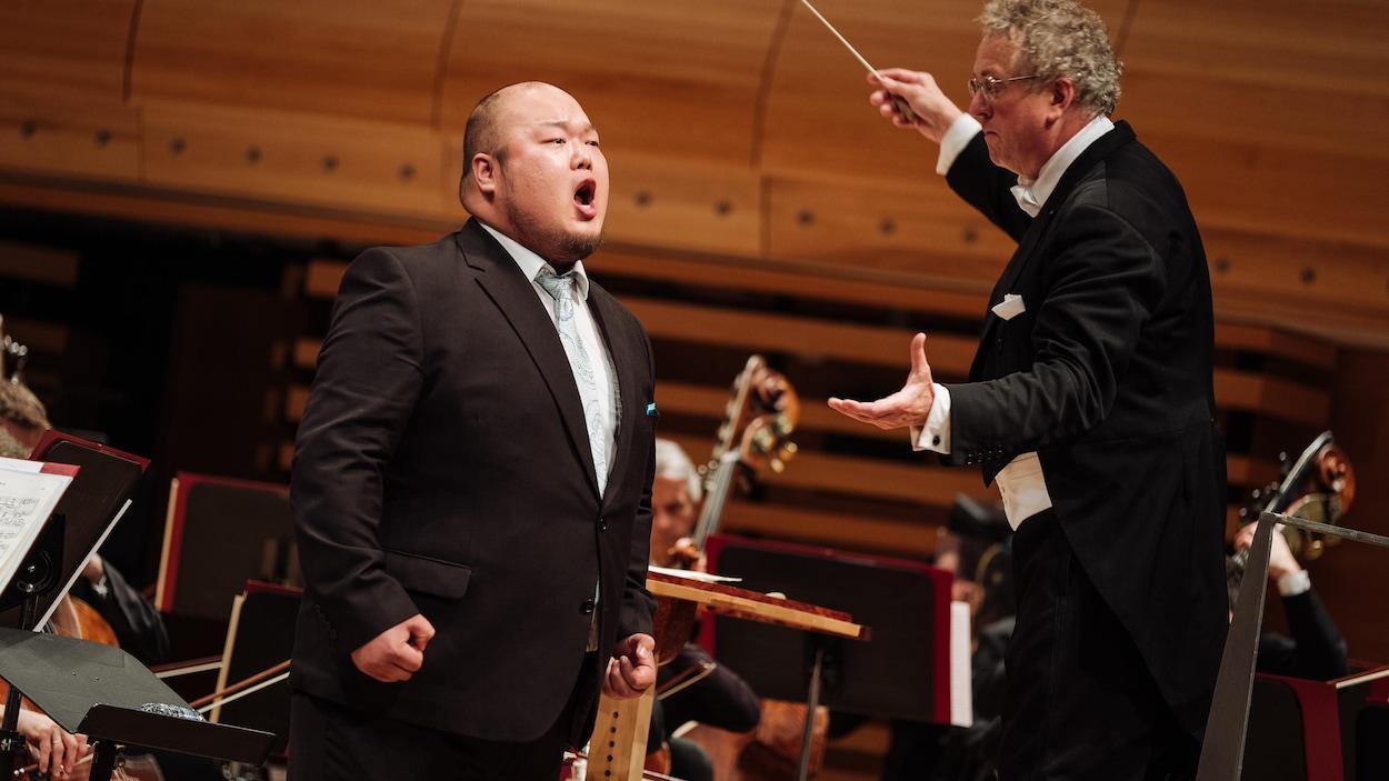 Un homme chante devant un orchestre.