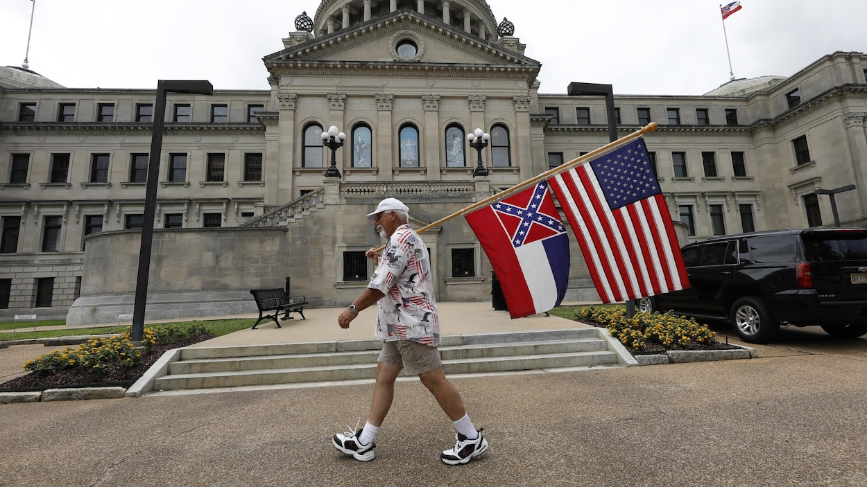 Un homme qui marche en portant le drapeau américain et celui du Mississippi avec l'emblème des Confédérés, un fond rouge surmonté d'un X bleu comptant 13 étoiles blanches.