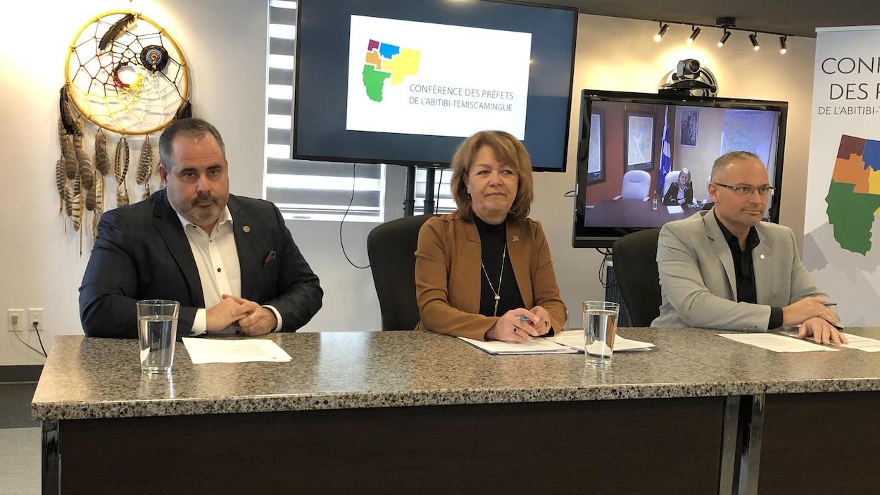 Martin Ferron, Diane Dallaire et Sébastien D'Astous derrière une table lors d'un point de presse, Claire Bolduc dans un écran de visioconférence.