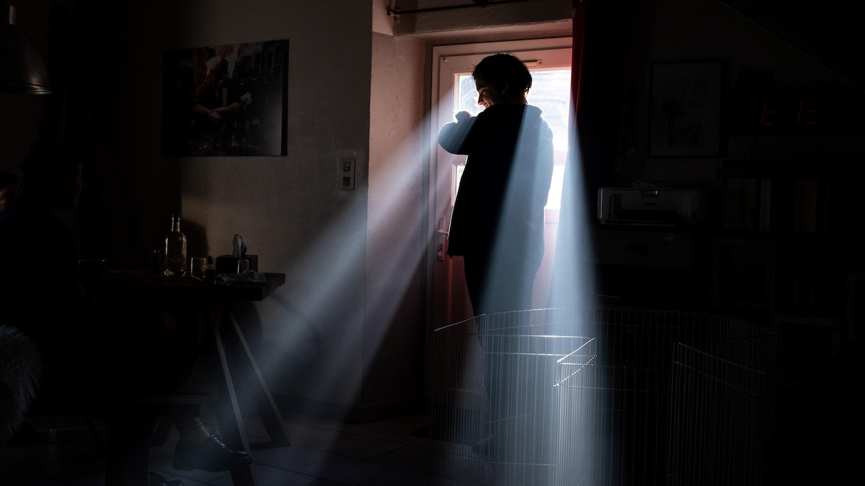 La silhouette d'une personne se profile devant une fenêtre par laquelle entrent les rayons du soleil.