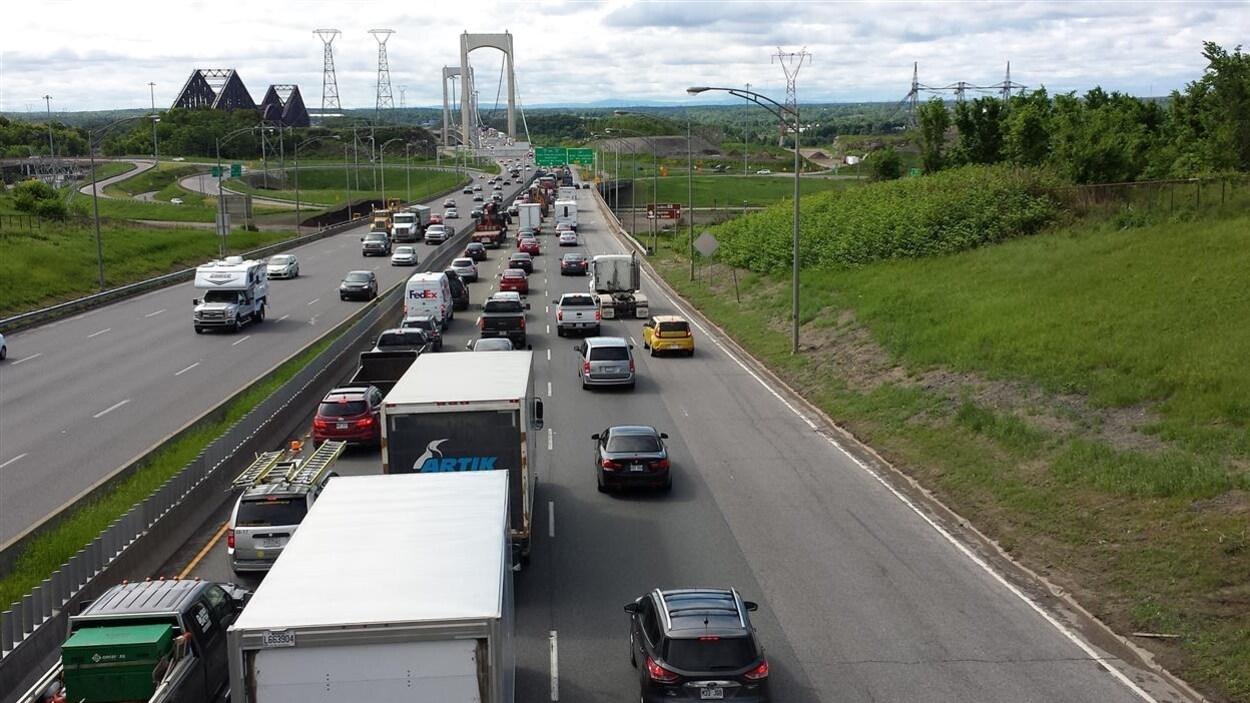 Des voitures circulent au ralenti sur l'autoroute Henri-IV, en direction sud, à l'approche du pont Pierre-Laporte, qu'on aperçoit au loin. Le pont de Québec est également visible. La photo a été prise de jour, en été.
