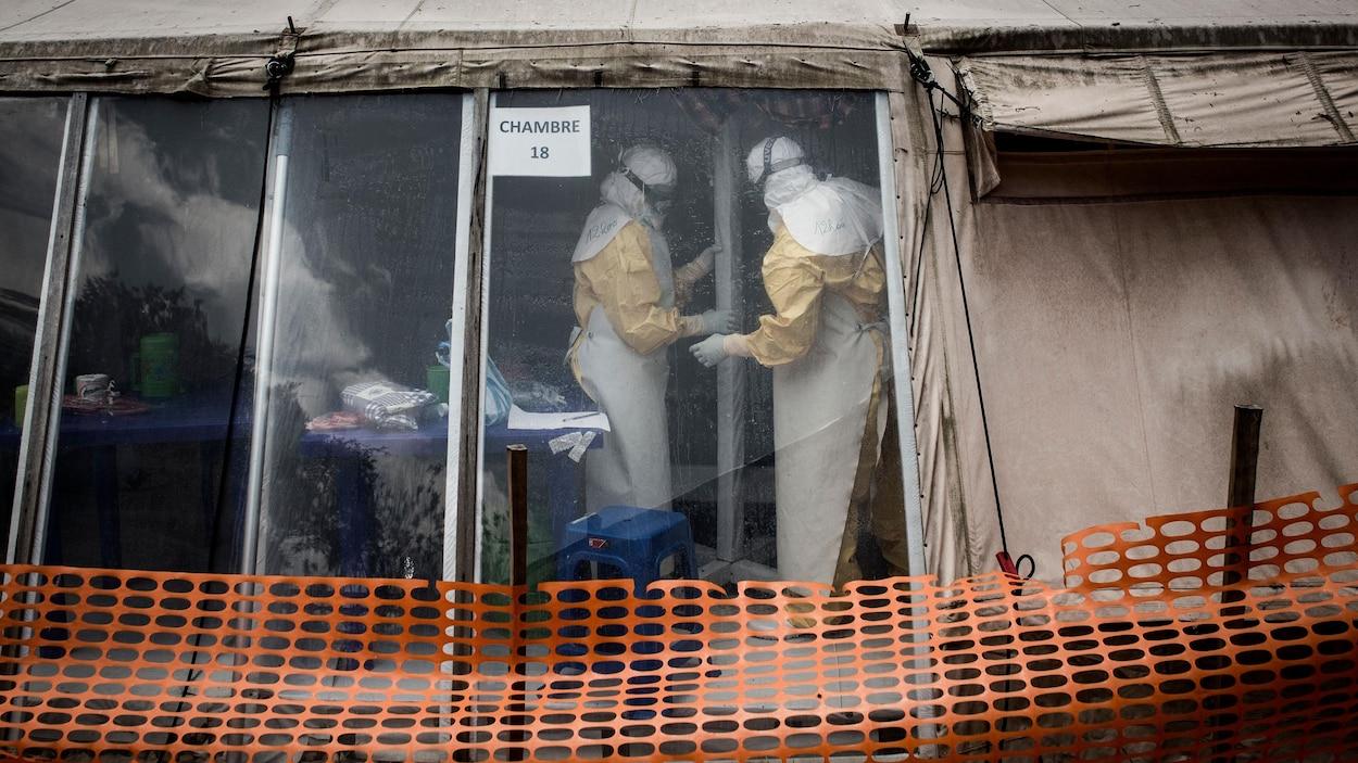 Des médecins en tenue stérile travaillent à l'intérieure d'une tente où l'on traite des patients atteints de l'Ebola.
