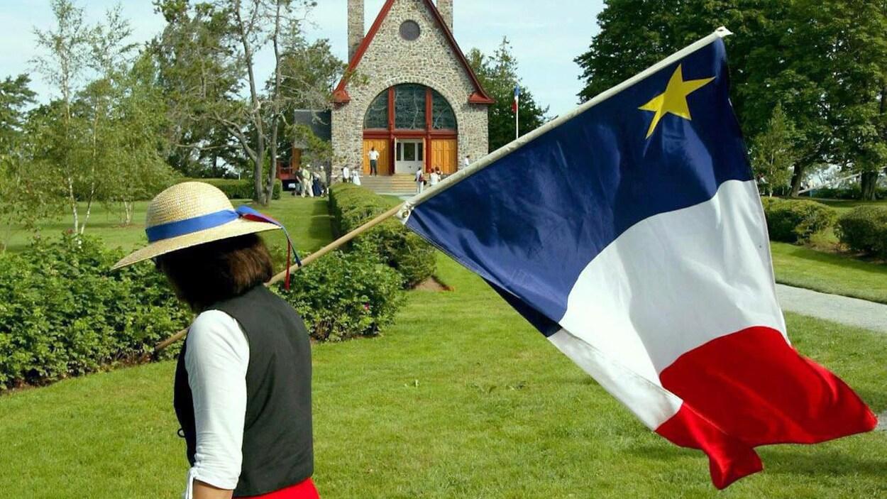 Jeanne (Doucet) Currie porte un drapeau acadien à Grand-Pré.