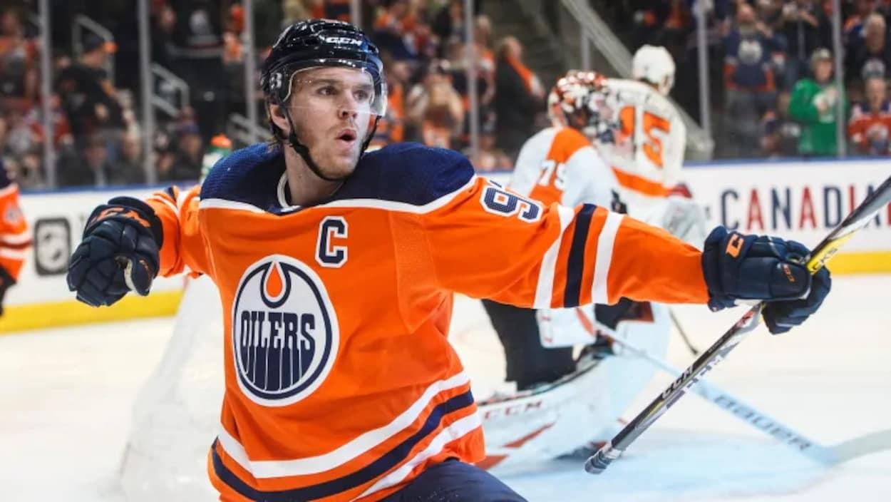 Il est sur la glace et célèbre un but.