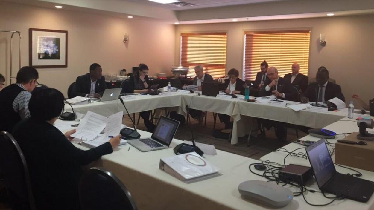 Les membres du conseil d'administration du CSF sont assis autour des tables formant un carré. Ils examinent des documents au cours de la réunion du conseil à Saskatoon.