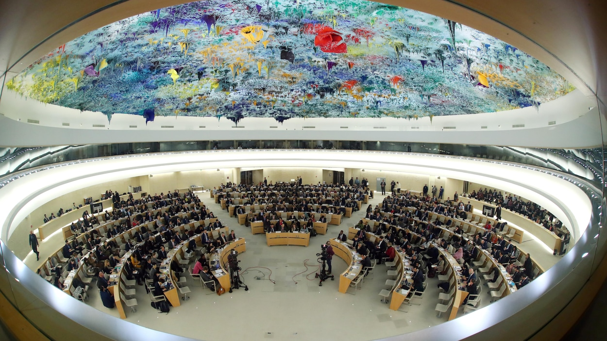 Des diplomates dans une grande pièce ronde dont le plafond est couvert d'une fresque multicolore.