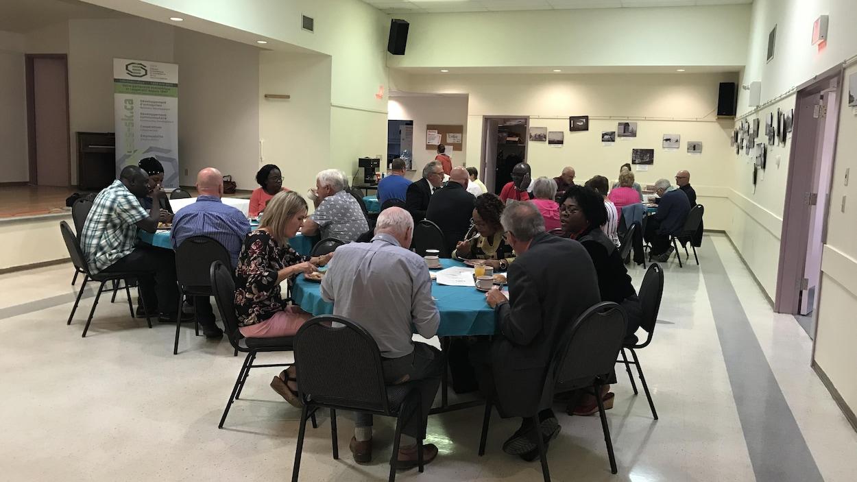 Une grande salle avec quelques dizaines de personnes assises autour de tables rondes.