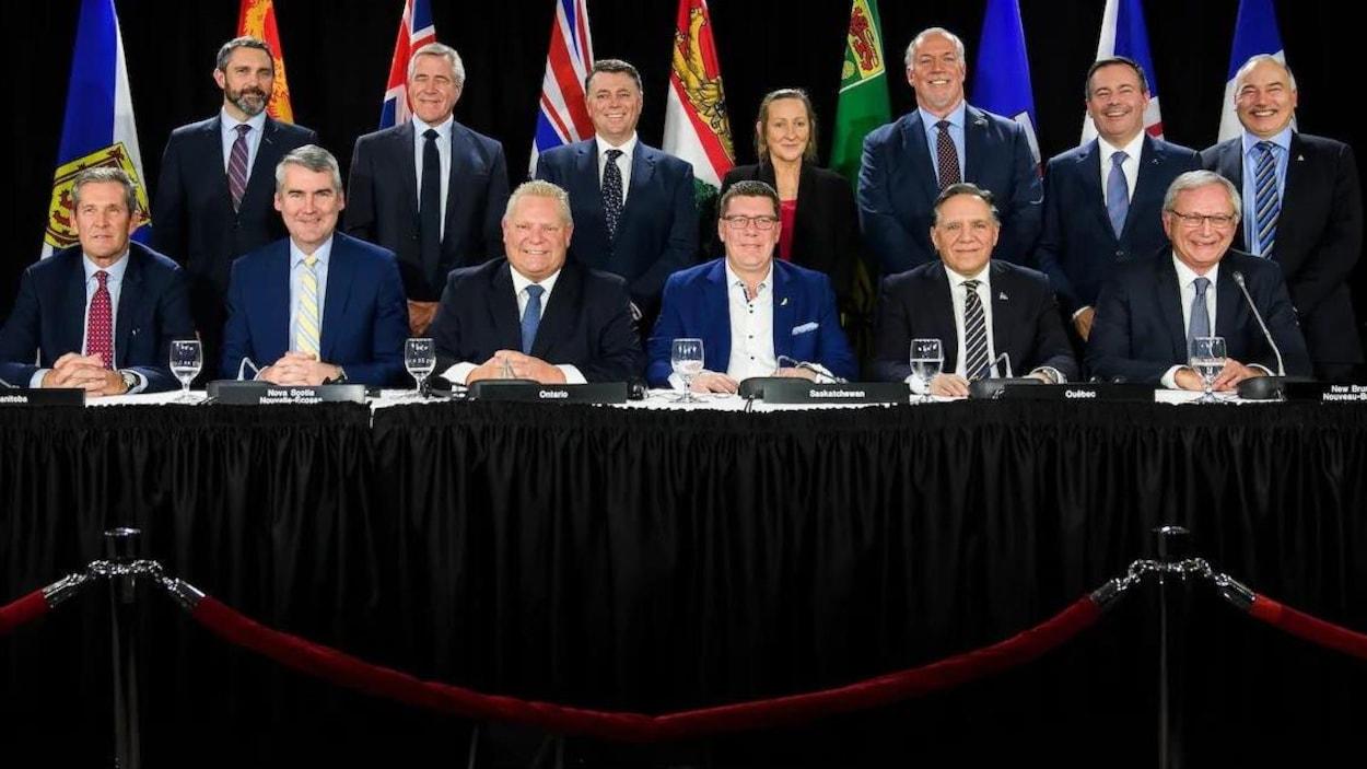 Les 13 premiers ministres des provinces et territoires canadiens sourient à la caméra, placés en deux rangées.