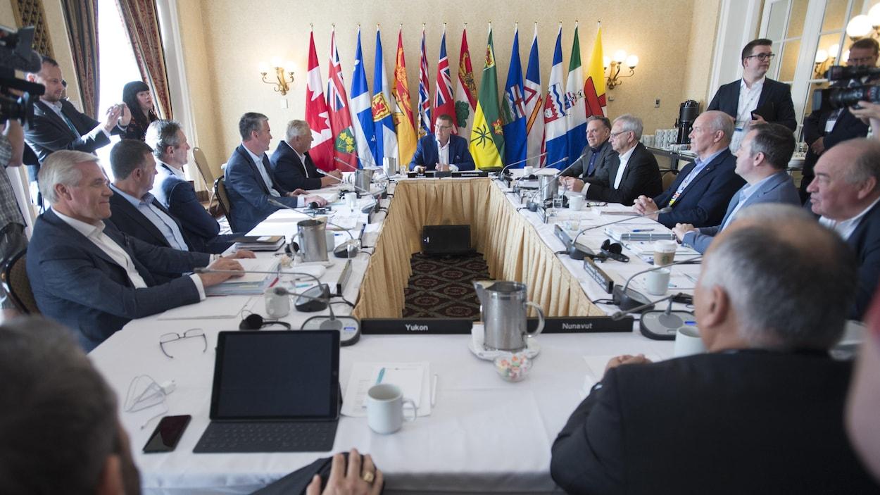 Tous les dirigeants provinciaux et territoriaux du Canada réunis autour d'une table au Conseil de la fédération à Saskatoon.