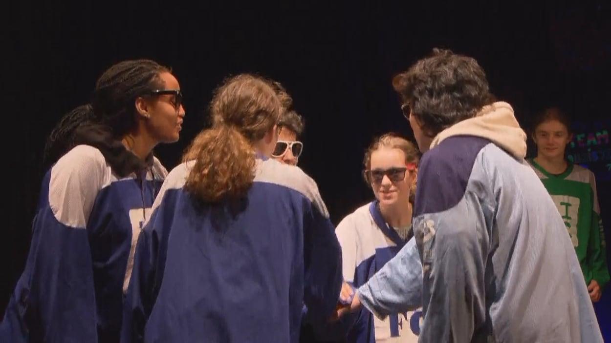 Cinq jeunes réunis en groupe sur scène participent au 30e anniversaire du Conseil jeunesse francophone.