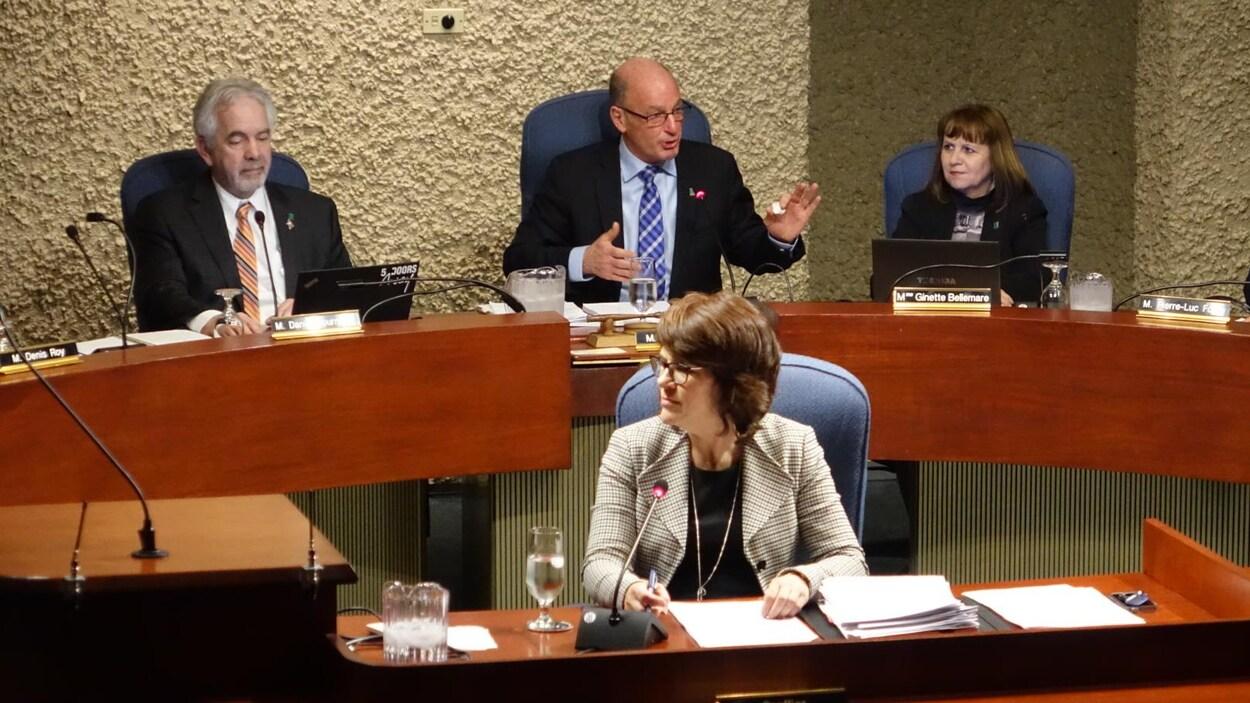 Le maire Yves Lévesque de face, qui gesticule, derrière la greffière, dans la salle du conseil municipal