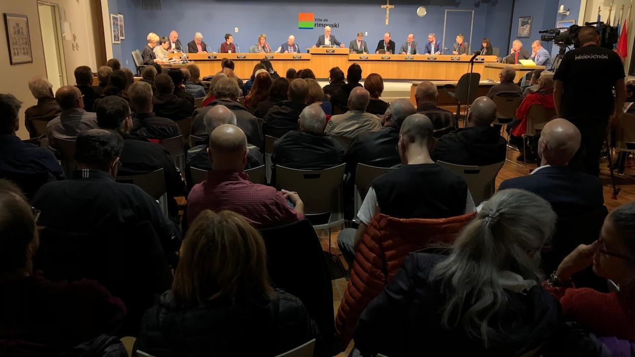Des citoyens sont assis dans la salle du conseil municipal de Rimouski, face au maire et aux conseillers municipaux.