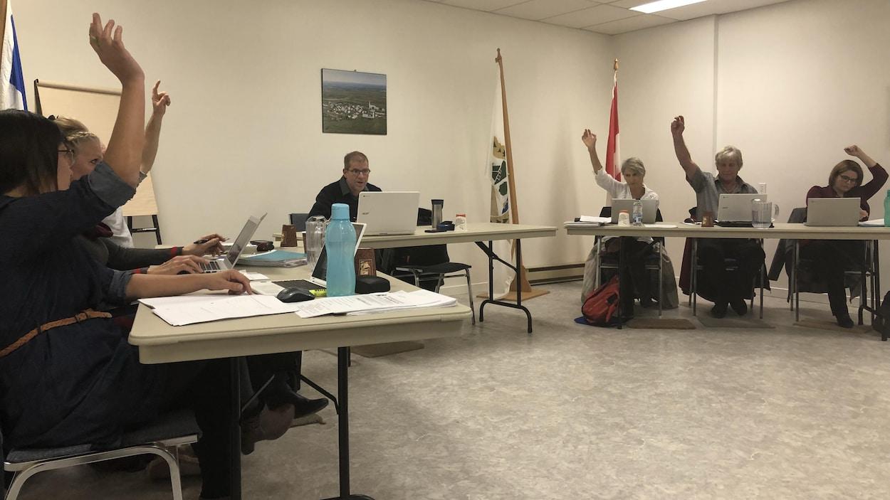 Le maire de Saint-Paul-de-la-Croix, Simon Périard et des conseillers municipaux votent sur une résolution.