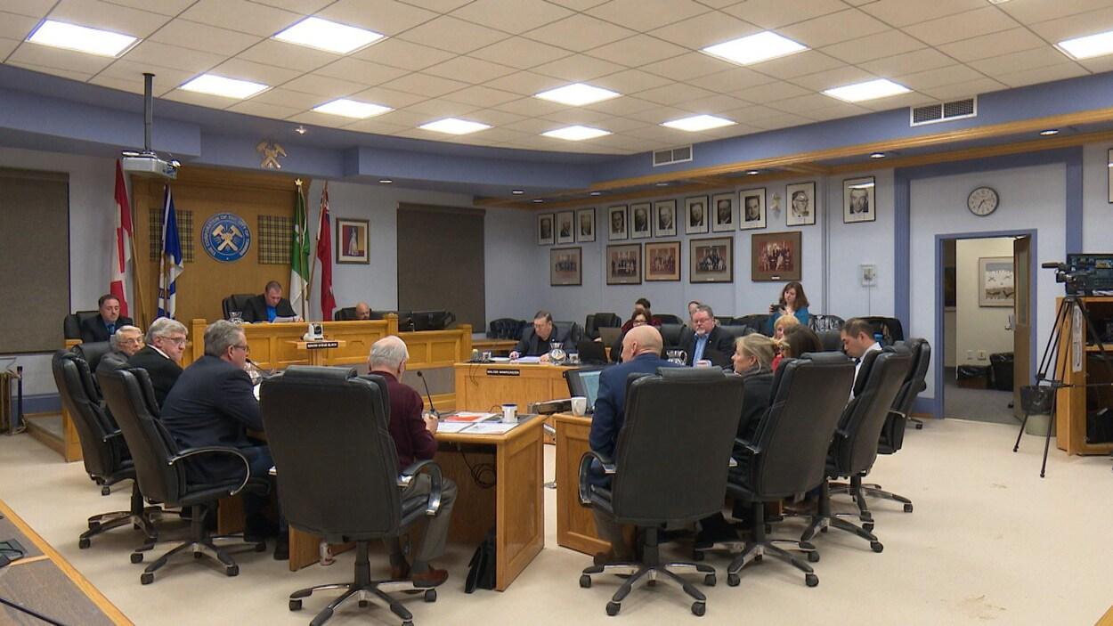Les conseillers sont assis autour de tables dans la salle de réunion du conseil municipal.