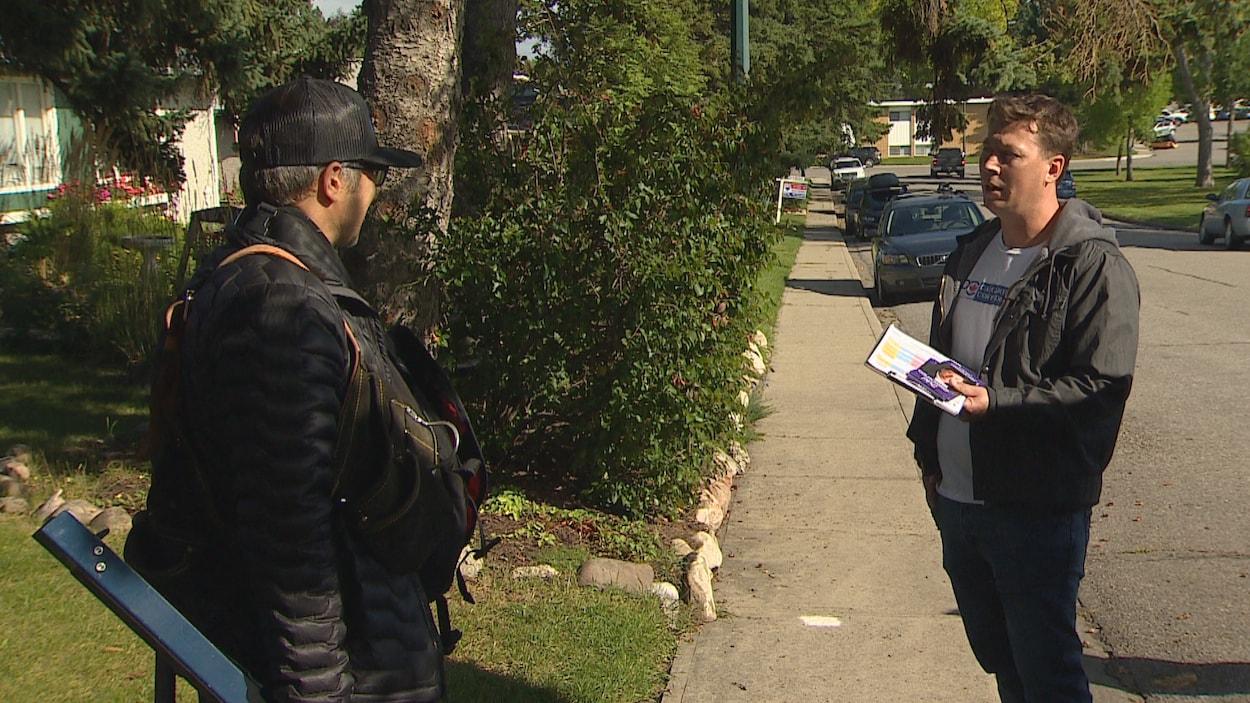 Un électeur discute avec Colin Korol sur une rue verdoyante.