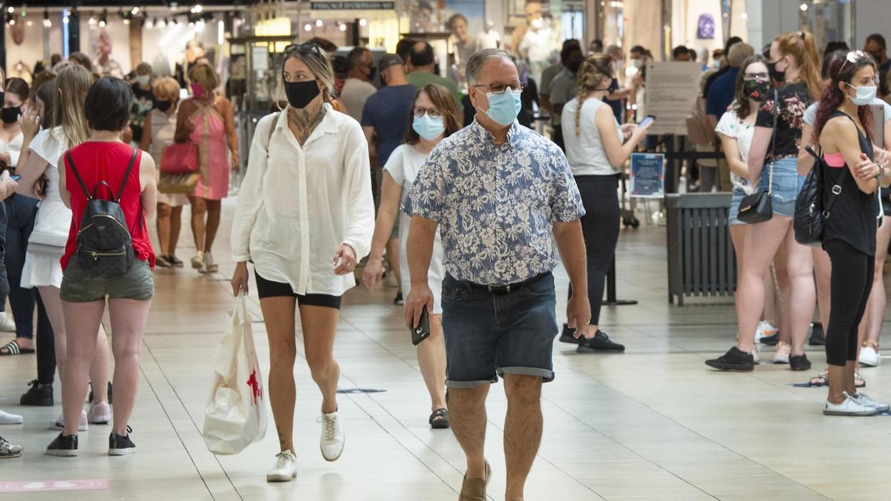 Des clients d'un centre commercial portant un masque.