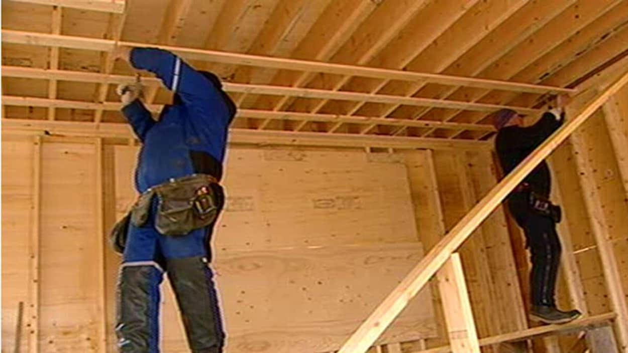 Travailleurs qui construisent une maison