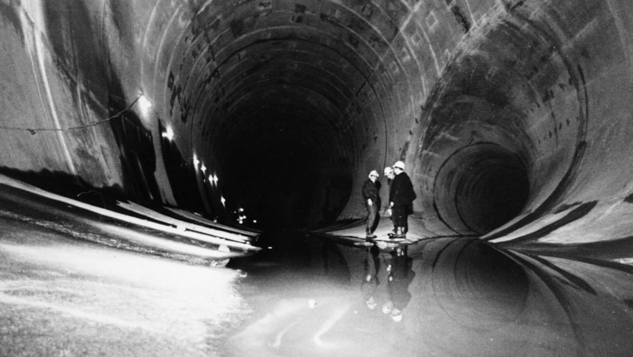 Des hommes à l'intérieur d'un immense tunnel.