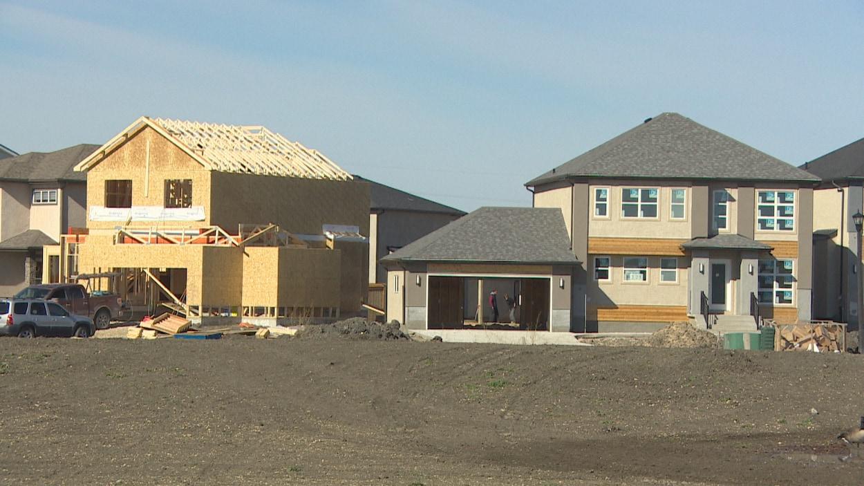 Deux maisons en construction, l'une est plus avancée que l'autre. Devant : une étendue de terre.