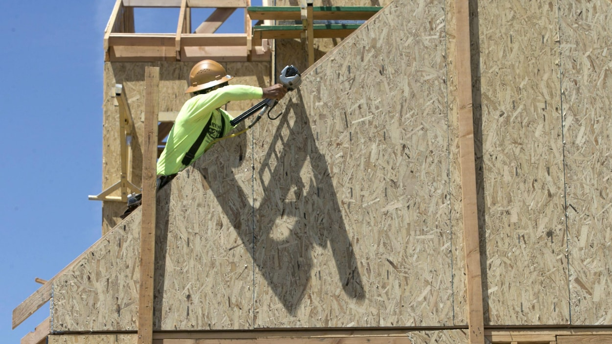 un travailleur de la construction est au travail dans ce qui doit devenir un bâtiment.