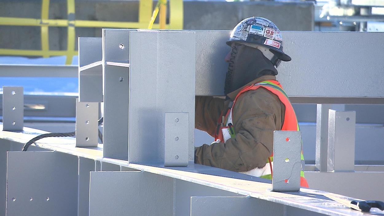 Un travailleur de la construction portant un capuchon sous son casque de protection pour travailler par temps froid durant l'hiver et ne pas perdre trop de chaleur par la tête.