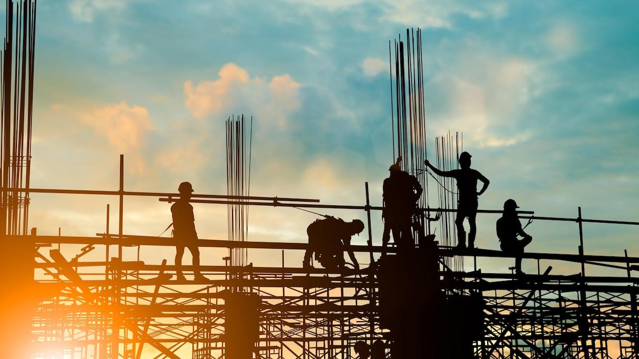 Les silhouettes de personnes sur une partie surélevée d'un chantier de construction sont vues lors d'un coucher ou lever du soleil. Ces personnes portent des casques protecteurs.