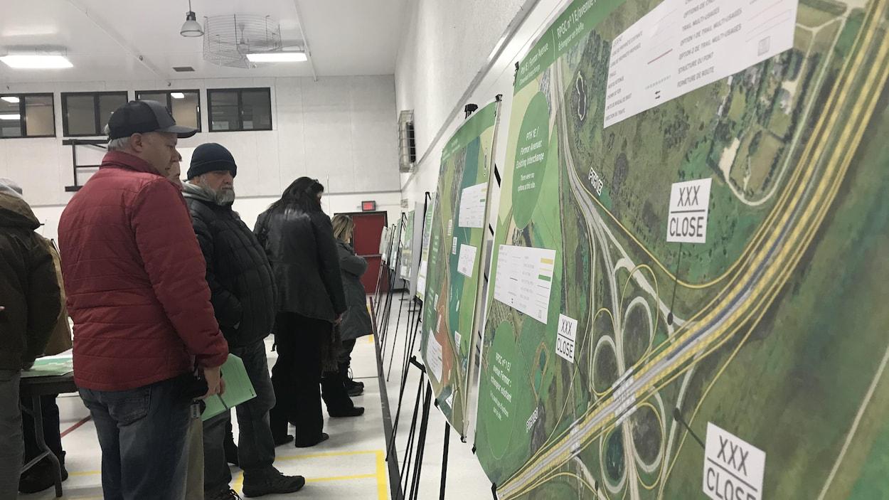 Plusieurs citoyens regardent des cartes illustrant diverses intersections.