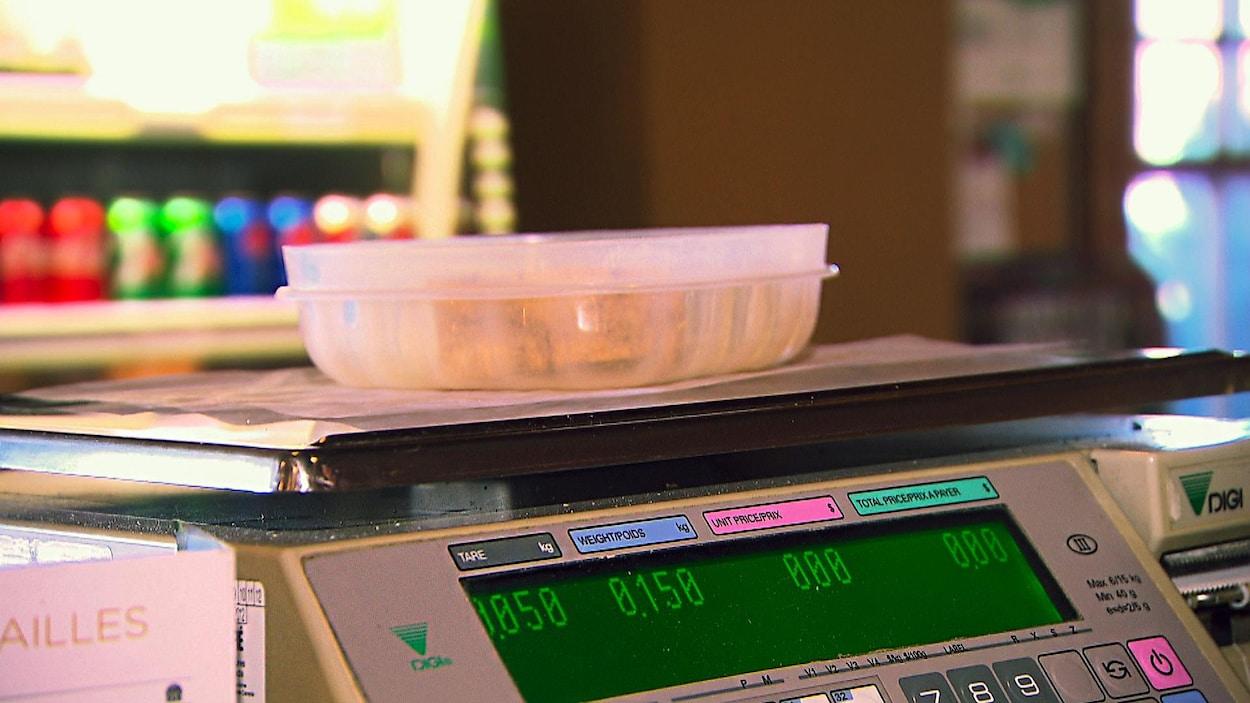 Un contenant de plastique réutilisable sur une balance à nourriture dans une épiecerie