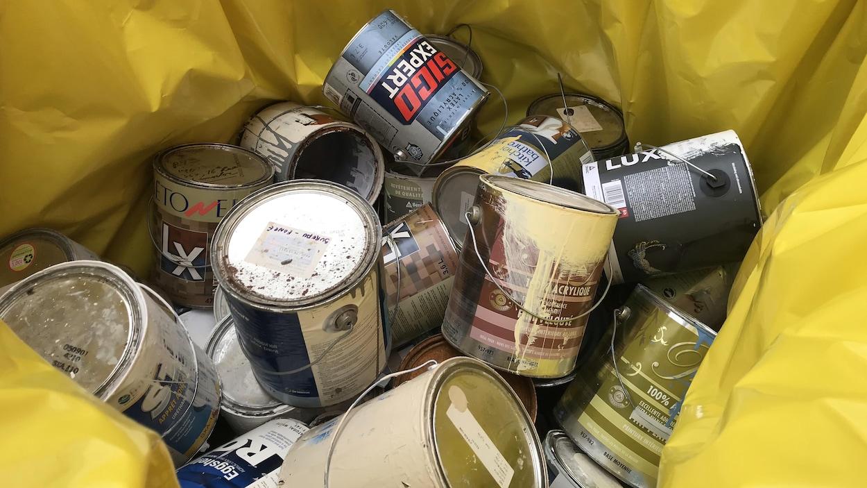 Des contenants de peinture dans un sac de plastique de couleur jaune