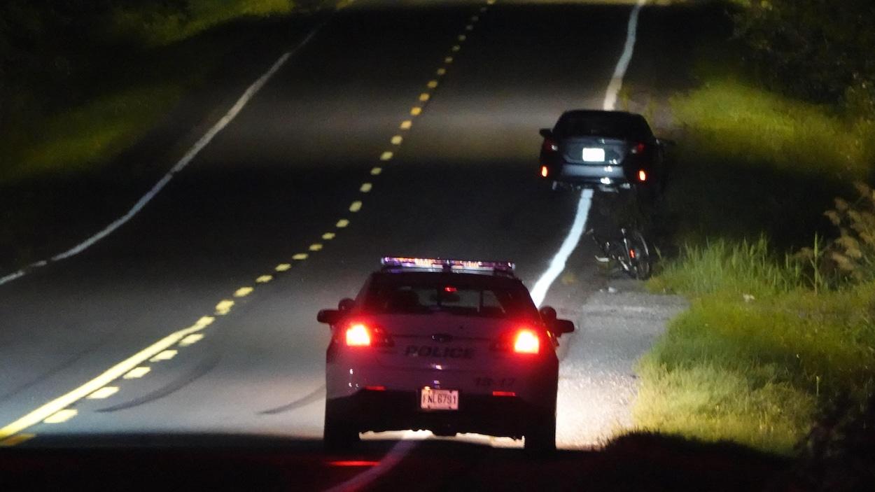 Une voiture de police éclaire un vélo et une autre voiture rangés sur le bord de la route.