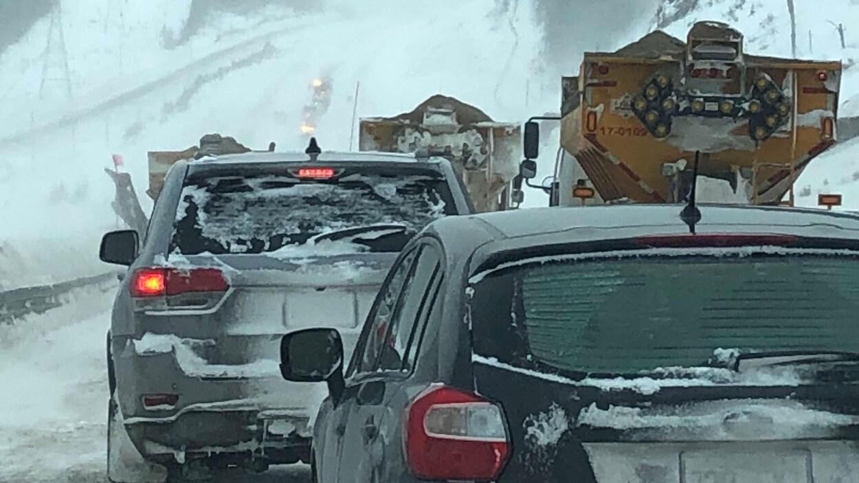 Une longue filée de voitures derrière trois déneigeuses.