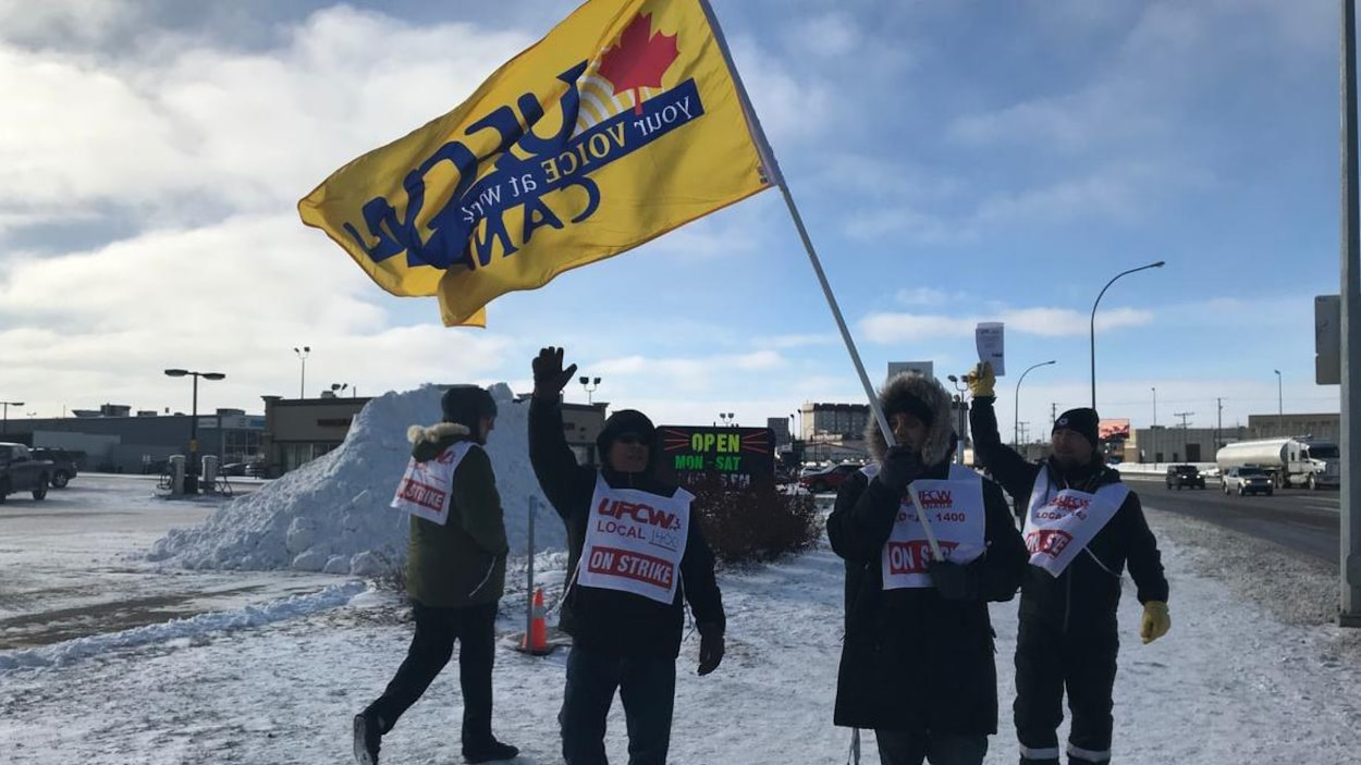 Quatre hommes en habits hivernaux manifestent sur un trottoir, portant des dossards aux couleurs de leur syndicat.