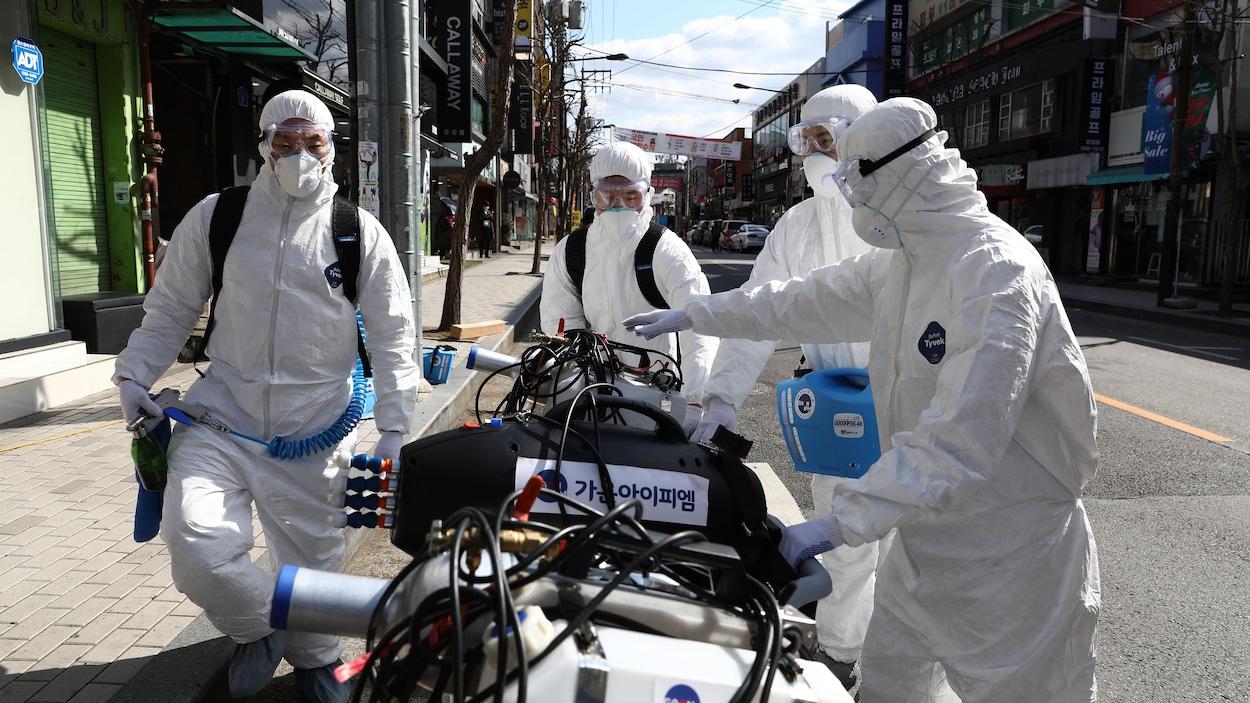 Quatre personne sont debout autour de machines servant à propulser du désinfectant.