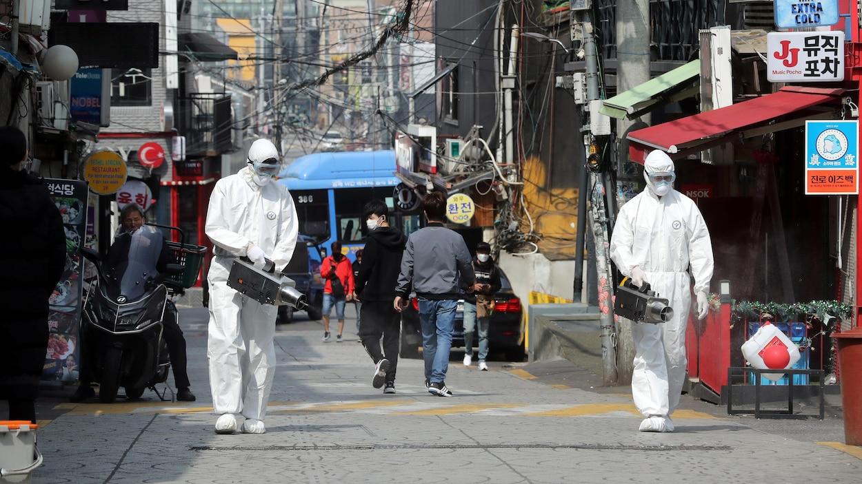 Deux hommes portant des vêtements de protection répandent du désinfectant dans une allée piétonne peu achalandée.